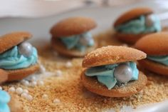 Under the Sea Party Oysters from DIY Louisville made with Vanilla Wafers, Shimmer Sixlets and Pearls, blue frosting, and a sprinkling of graham cracker crumbs.