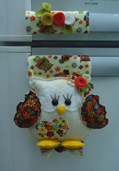 Confeccionado em feltro e tecido tricoline 100% algodão, com enchimento de fibra siliconizada antialérgica. <br>Produto 100% artesanal, peça exclusiva, lavável. <br>A corujinha possui aproximadamente 15 cm. <br>Acabamento com apliques, flores e folhas de feltro e fios de rami. <br>O fechamento é feito com velcro, o que possibilita um ajuste perfeito ao seu refrigerador. <br> <br>Obs.Se quiser, ao fazer sua encomenda especifique as cores predominantes desejadas para o tecido e as flores.