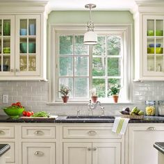 Light-reflecting finishes and windowed upper cabinets create the illusion of space in this narrow kitchen redo. |  Photo: Tria Giovan | thisoldhouse.com