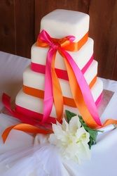 Square 4 tier wedding cake with hot pink and bright orange ribbons.  Nebraska.