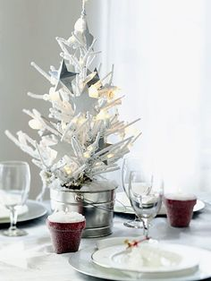 A table blanketed in white lends sophistication and a sense of occasion to any gathering. Get the look by using clear glass and metallic elements against a backdrop of white table linens and china. An artificial tree spray-painted white, flocked with spray snow, and potted in a galvanized pail makes a modern centerpiece for this table. Lights and star ornaments hung on the tree add another layer of sparkle.