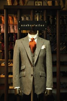 Beautiful single-breasted olive green suit punctuated with an orange tie to match the stitch on the lapel.