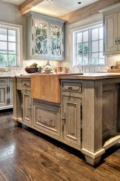The custom island in the kitchen features a butcher block, a sentimental piece that has been in every home Gene has owned, inset into French Oak. The cabinets, finished by Segreto Finishes, are all raised to resemble pieces of furniture. The hardwood floors throughout the home are waxed red oak with ebony stain, added after the homeowners moved in.