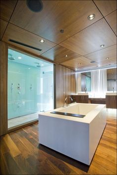 Floor to ceiling glass shower with two shower heads. Also love this rectangular bathtub that sits in the center of the bathroom. Although the hardwood looks amazing i'm not sure i love the idea of it in a bathroom.