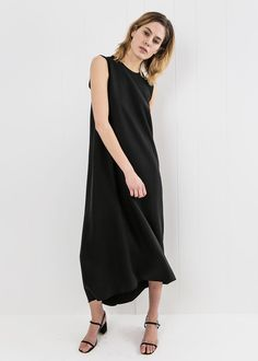 Meteorite black maxi dress featuring a unique overlap at back. Sleeveless. Rounded neck. Zipper at right shoulder. Relaxed fit. Mindfully designed and crafted in Kaarem's own fair trade production studio based in Ho Chi Minh City, Vietnam. Worn with the Rafa simple sandle in sloe. CARE Dry clean only. MATERIAL 100% lyocell. LYOCELL / Otherwise known as Tencel, Lyocell is an extremely gentle fibre made from the wood pulp of Eucalyptus trees that it is both biodegradable and recyclable...