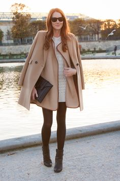 camel cape coat, black clutch, white cable-knit sweater dress, black booties