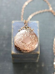 A gorgeous 100 year old Edwardian rose gold locket is hand engraved with an intricate pattern of flowers and swirls with a classic shield like center