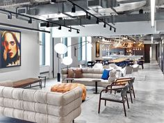 WME/IMG's Office by the Rockwell Group Lets Talent Shine  At the Rockwell Group's New York office for WME/IMG, the demonstration kitchen's custom lighting truss in painted steel incorporates a mirror, which reflects a mixed-media portrait by Adam Hunter Caldwell. Photography by Eric Laignel.