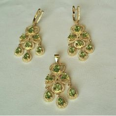 "Peridot Chandelier Set 14K yellow gold plated solid sterling silver and they are marked 925. Chandelier style earrings and pendant are set with teardrop and round natural peridot and encrusted with tiny white cubic zirconia. Lever back closure on the earrings. They measure 2"" long. The details on these are amazing. Brand new from the manufacturer. Jewelry Earrings"