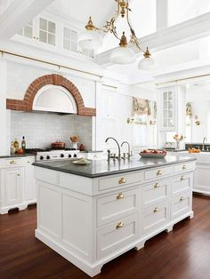 Stylish brass hardware on white cabinetry; beautiful kitchen with terrific natural light and brick accent.