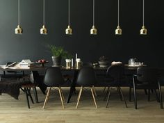 black wall, black eames chairs and brass plated steel pendant lamps by Alvar Aalto A330S