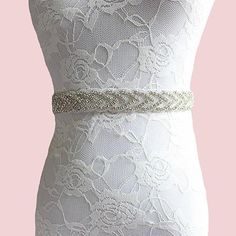 "Accentuate your waist and bring some detail downward with this gorgeous rhinestone and satin ribbon belt. Product Details: 1"" H x 47"" W 1"" H x 17 1/2"" crystal o"