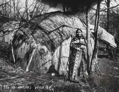 Ioway Indian woman in front of a mat lodge (indian house)