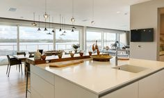 Lakeside view from the bulthaup b3 kitchen island with a glacier white Corian workstop and Quooker Fusion mixer tap. A Jonathan Field breakfast bar provides natural beauty and warmth.