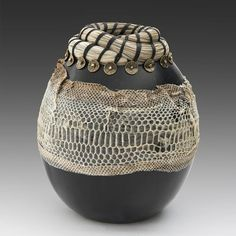 Porcelain vessel, pit fired and papered with an snake skin. Woven with horse hair and brass beads and waxed thread.