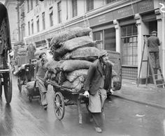 Porters transport large sacks of vegetables, probably potatoes, by push cart or trolley along a street in London's Covent Garden. Vintage London, Old London, London History, Tudor History, British History, The Blitz, Covent Garden, World War Two, London England