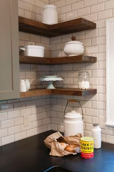 White subway tiles on washer/dryer wall with dark wood open shelving