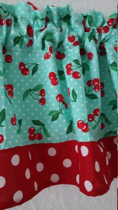 This cute kitchen valance is made from a lightweight cotton fabric by Michael Miller called Cherry dot. It has a pretty soft blue background with tiny white dots and cherry bunches scattered across it. The top has a ruffled rod pocket across it and the bottom is trimmed with a 4 bright red with white polka dot fabric. This valance will be perfect in retro kitchens, or if you just like fun and whimsical.  This valance measures 16 1/2 long by 42 wide so it will fit perfect on kitchen door...
