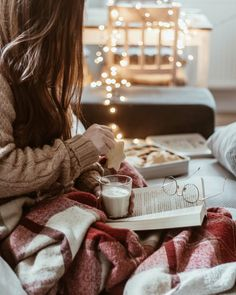Hygge life reading a good book eating cookies and drinking milk in a cozy sweater and plaid blanket.