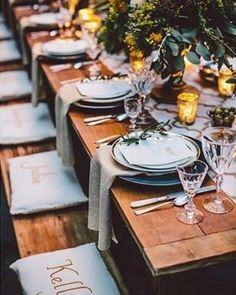 Linda decor de mesa num casamento no estilo rústico chic, com detalhes em azul aqua, cobre e mahogany (uma cor marrom avermelhada, parecida com a madeira de mesmo nome).  A mesa e o banco de madeira, flores e velas, trazem os ares do rústico e os utensílios, com detalhes em cobre, trazem o luxo. ✨ E o que são essas almofadas personalizadas para marcar o lugar dos convidados com seus nomes? Ideia top, que além de dar um toque pessoal, a almofada dá um conforto maior ao sentar à mesa e, ao...