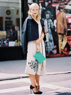 Black leather jacket, white top, light grey skirt, green clutch, and black heels