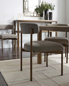 Sleek and chic Remy dining chair with curved back and floating seat. Shown in vintage brass finish; also comes in polished stainless steel finish. Can be upholstered in fabric or leather.