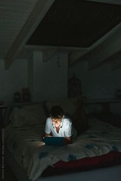 Young woman using technology in the bedroom in the night by Simone Becchetti for Stocksy United