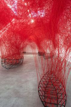 Complex Web of Red Thread Swarms Above Stranded Boats as a Meditation on Fate…