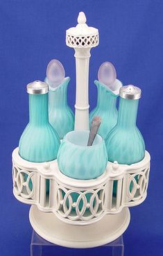 QUILTED DIAMOND SATIN GLASS CASTOR SET IN CASTLEFORD CREAMWARE STAND:5 blue stretched diamond glass bottles, mustard, 2 shakers and 2 cruets Victorian Bride, Old Glass Bottles, Vintage Cake Stands, Condiment Sets, Displaying Collections, Carnival Glass, Antique Glass, Milk Glass, Colored Glass
