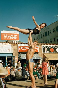 """Ed Fury lifting Abbye """"Pudgy"""" Stockton at Santa Monica's """"Muscle Beach"""", photographed by Bob Mizer (1951). Bodybuilding culture and Mizer's photography had a substantial gay following in that earlier era. The Purser Apartments building, visible in the background, still stands at 1659 Ocean Front Walk."""
