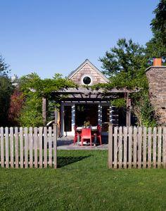 An outdoor dining area beneath a pergola.