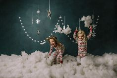 holiday mini session photo shoot christmas pajamas sisters siblings silver hanging stars blue backdrop puffy cotton clouds reindeer Holiday Mini Session Ideas, Cotton Clouds, Hanging Stars, Christmas Pajamas, Mini Sessions, Boudoir Photographer, Siblings, Reindeer, Photo Shoot
