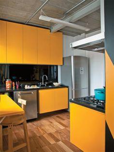 Desenhados pela arquiteta Suzana Barboza, a mesa dobrável e os armários da cozinha são de MDF revestido de laminado plástico amarelo. Na parede atrás da bancada de granito, o painel de vidro serigrafado preto (Divinal Vidros) arremata o conjunto.
