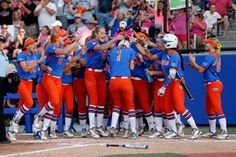 Gators catcher Aubree Munro, No. 1, is greeted at home after her third-inning home run Monday.