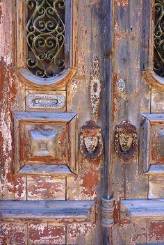 old door, faces as knockers photo by Filipa Lobo