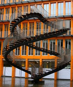 "The sleek steel of this 30-foot-tall double-helix staircase pops against the backdrop of an orange-and-glass vertical office tower. Located in the courtyard of the global accounting firm KPMG Deutsche Treuhand-Gesellschaft since 2004, Umschreibung (or ""rewriting"" in German) is the creation of the Danish artist Olafur Eliasson. The staircase doesn't actually lead anywhere and isn't open to the public to climb, but it certainly makes a statement."