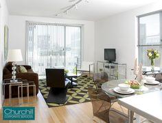 Spacious living area with expansive windows offering an abundance of natural light and sleek hardwood flooring