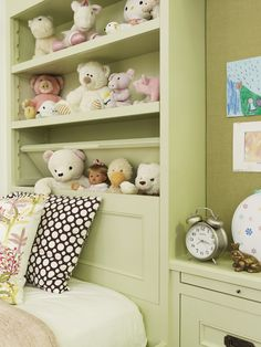 Adorable girls bedroom with powder green built-ins featuring hidden teddy bear cubby and pull out nightstand area.