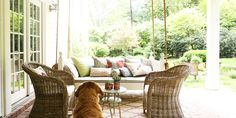 with succulents planted in old coffee cans sit on a soft outdoor rug laid over the brick-paved space. Family dog Shug loves hanging out on the porch, too, eagerly looking for a squirrel to chase.   - CountryLiving.com