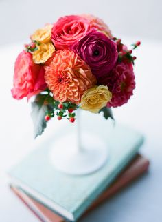 Bright blooms in pedestal vase and covered books.  Photo by lindsey ocker photography.  www.facebook.com/sweetanniefloral.com