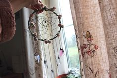 A whimsical crystal dream catcher with fairy wings, angel aura quartz and pink roses. This magical piece has been bound in taffeta and adorned with flowers.