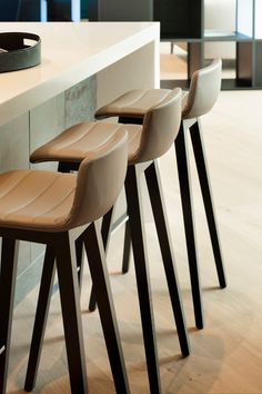 Beige leather stools with wooden legs create a high-end finish for this office design