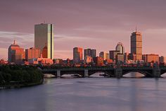 Boston Last Light kissing the city skyline photography at sunset showing famous landmarks such as John Hancock building, Prudential Center and Longfellow Bridge while the sky is on fire displaying orange, pink, purple and red sunset colors.  Skyline photography images of Boston are available as museum quality photography prints, canvas prints, acrylic prints or metal prints. Prints may be framed and matted to the individual liking and decorating needs.  www.RothGalleries.com