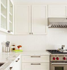 Kitchen with white cabinets and white subway tile backsplash design by Studio Gild.