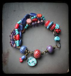 """Vibrant, fun multistrand bracelet with 3 polka dotted lampwork focals by Mindy Macgregor and Ellen Dooley, resin charm by Jade Scott, copper and lampwork clasp by Genea, and lampwork charm by Jasmin French. Four hand knotted strands that include Lapis nuggets, red coral, and assorted Czech glass. Fits a 6-6.5"""" wrist, a short chain tail can be added for larger sizes, and a charm would be attached to the end of it, please make sure to request this addition in your order comments if desired."""