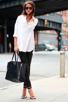 Mulher posa para foto de street style usando camisa branca, calça de couro preta, sandália de tiras, óculos escuros e bolsa saco preta