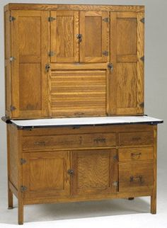 kitchen & household, Indiana, An oak Hoosier cabinet [or baker's cabinet] with enameled top, [paneled doors and sides], original white enamel flour sifter. Metal tag reads Napanee Dutch Kitchenette.