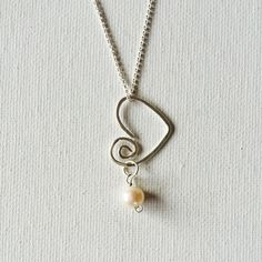 Made a silver spiral wire floating heart necklace with freshwater pearl!
