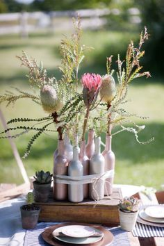 Bottle centerpiece --- we can save all of our wine bottles and such, spray paint, and wrap in burlap and ribbon -- stick baby's breath and flowers in them for the tables! (Could also add those picture holder sticks and put some of those in, too!)