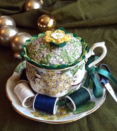 A teacup pincushion. I LOVE it! And her price is realistic.